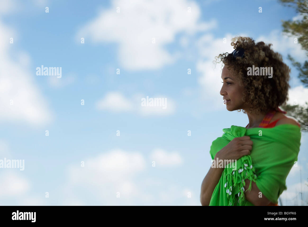 Woman standing outdoors with shawl wrapped around shoulders, side view - Stock Image