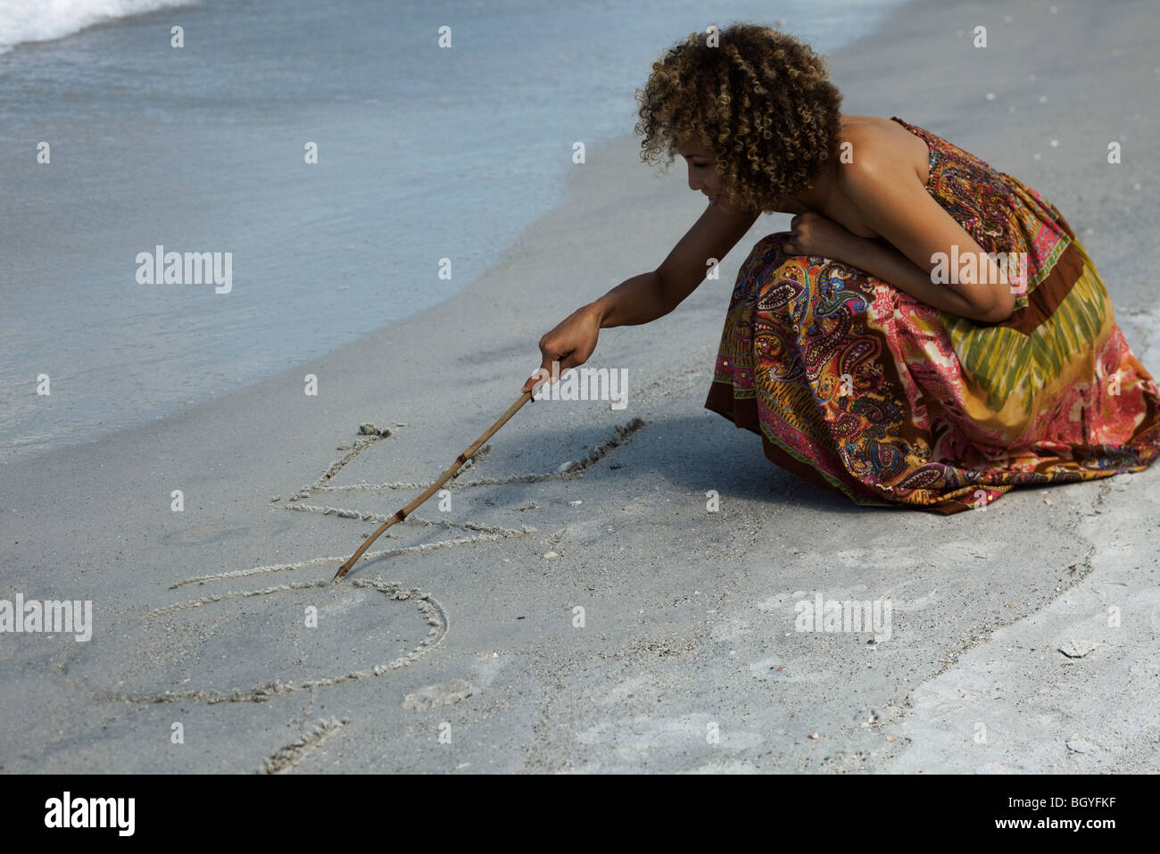 Woman at beach, writing 'love' in sand with stick - Stock Image
