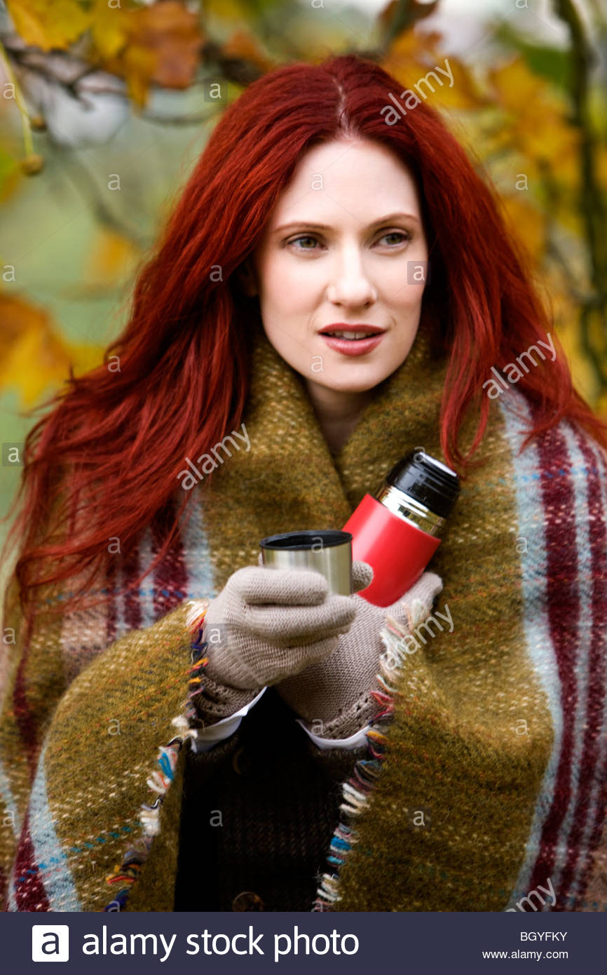 Portrait of a young woman wrapped in a blanket, holding a flask - Stock Image