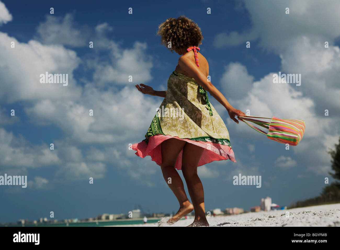 Woman in sundress spinning on beach - Stock Image