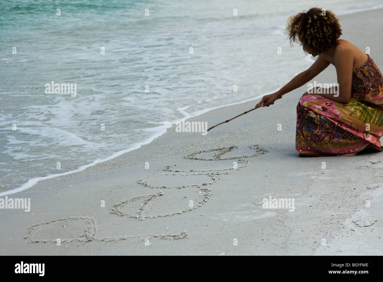 Woman crouching on beach, writing word 'peace' in sand with stick - Stock Image