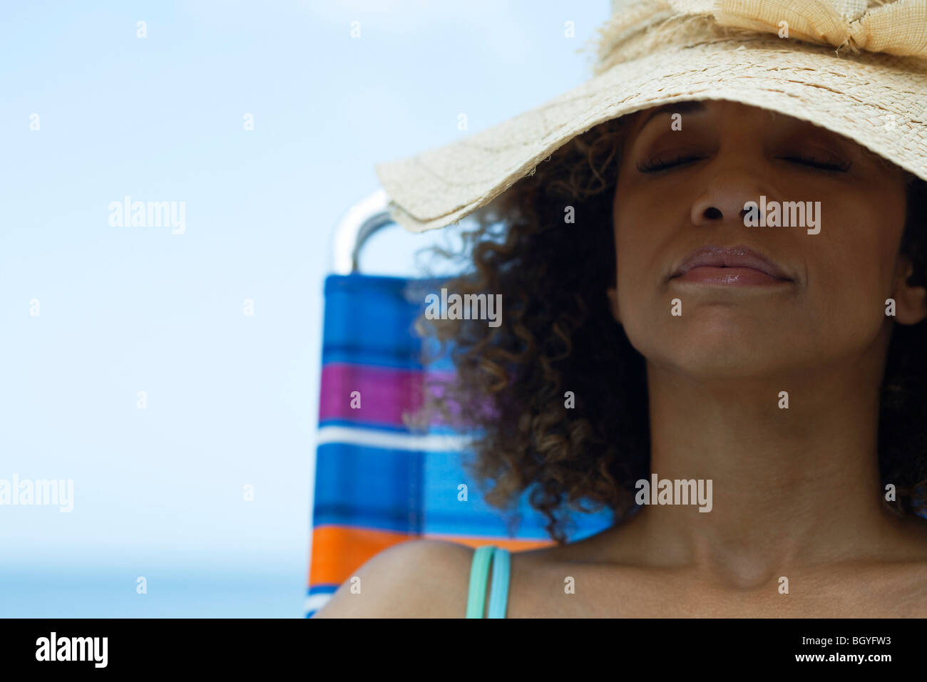 Woman sunbathing on deckchair, wearing sun hat - Stock Image