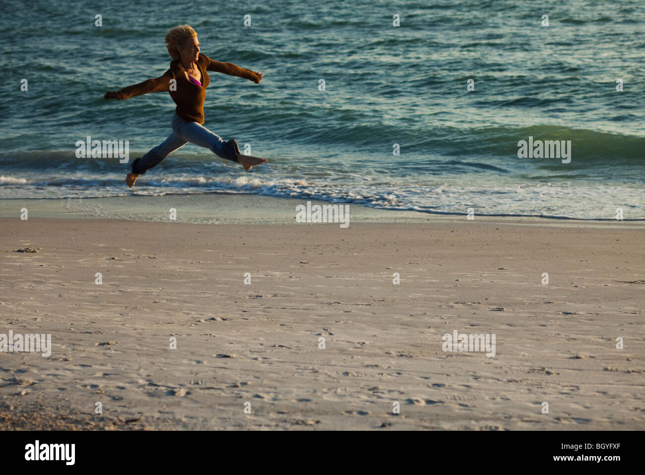 Woman leaping in midair at beach - Stock Image