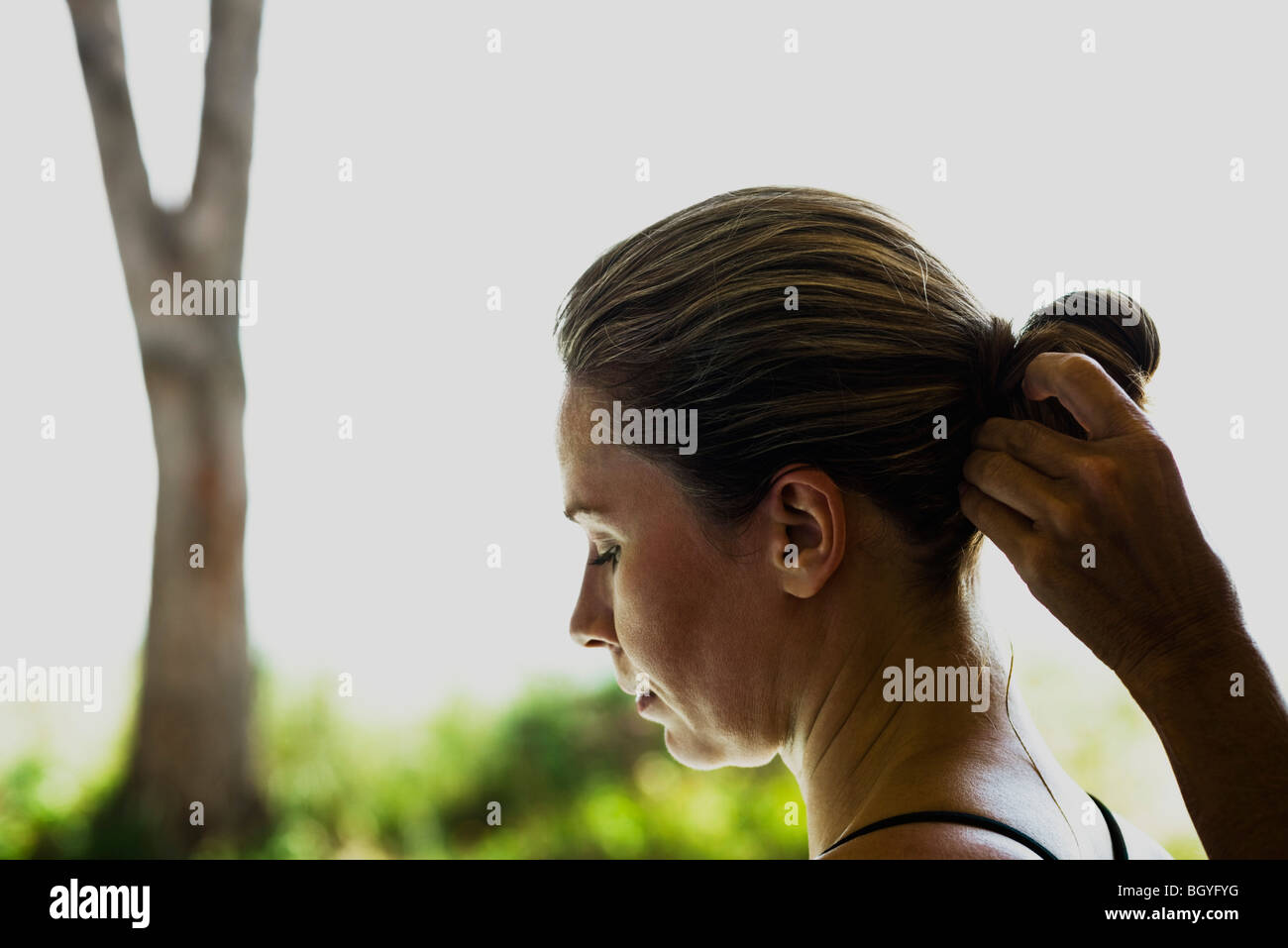 Woman having hair styled, side view - Stock Image