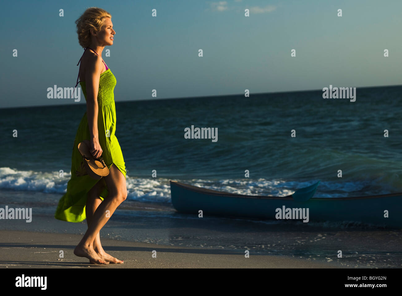 Woman in sundress walking on beach, looking at sea - Stock Image