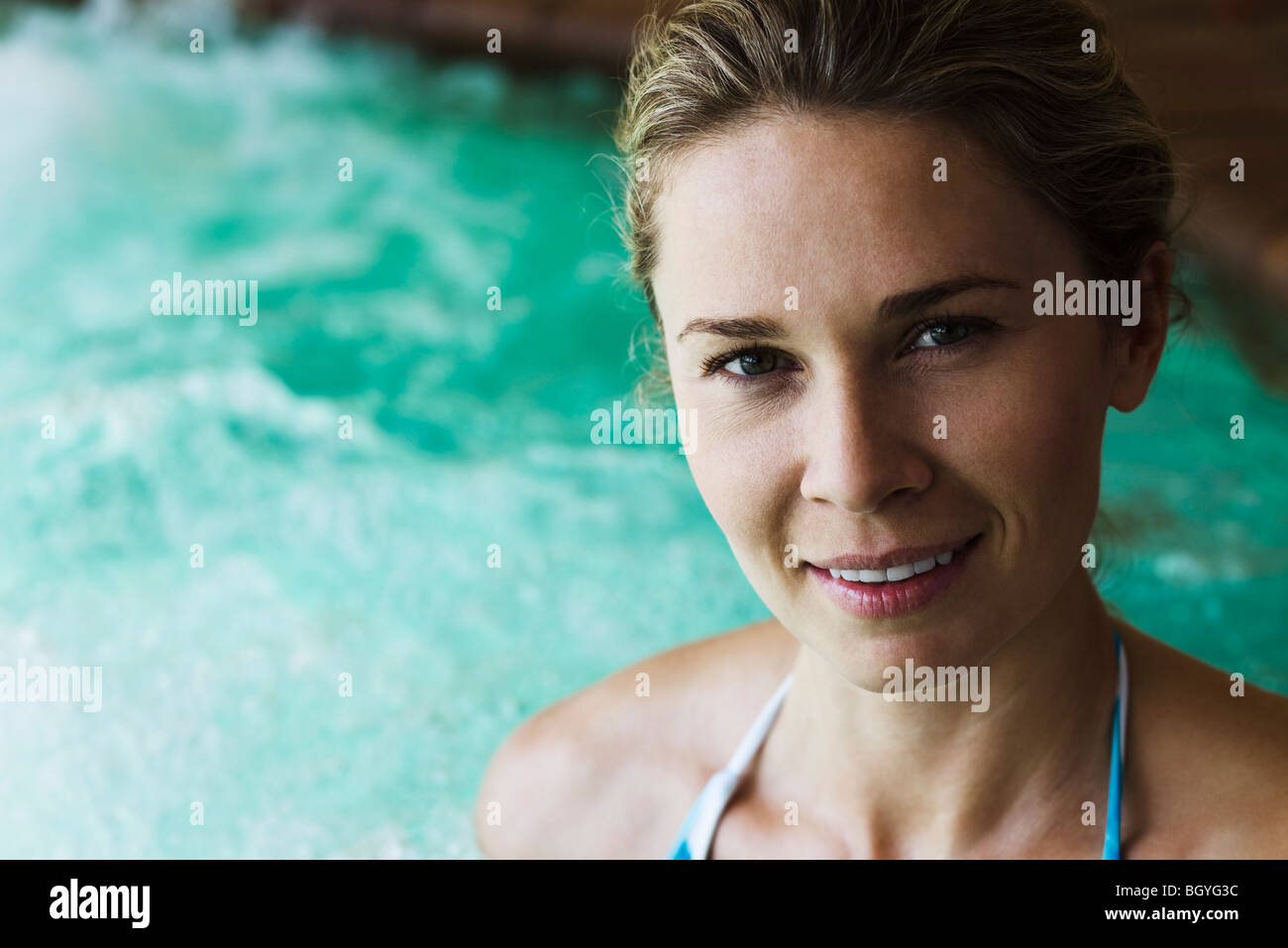 Woman smiling at camera, hot tub in background, portrait - Stock Image
