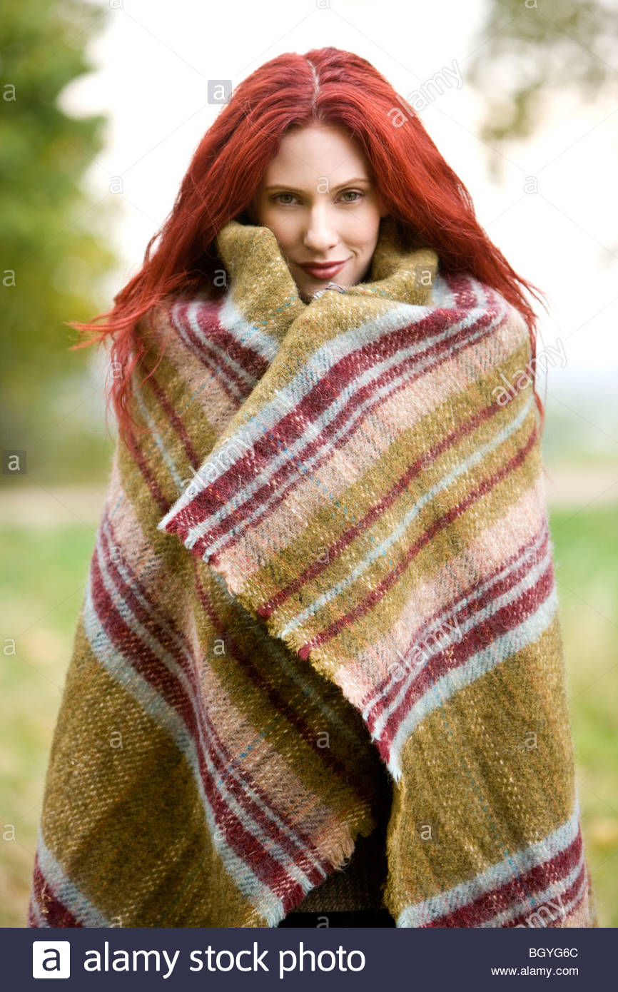 Portrait of a young woman wrapped in a blanket - Stock Image