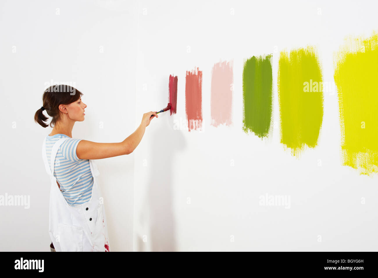 Woman painting colour swatches on wall - Stock Image