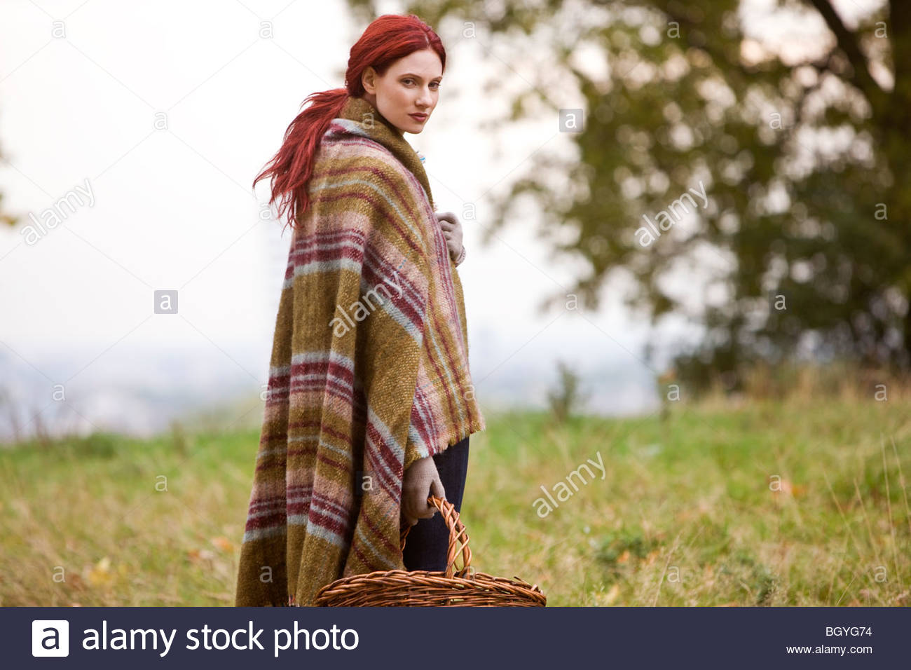 A young woman wrapped in a blanket, holding a wicker basket - Stock Image