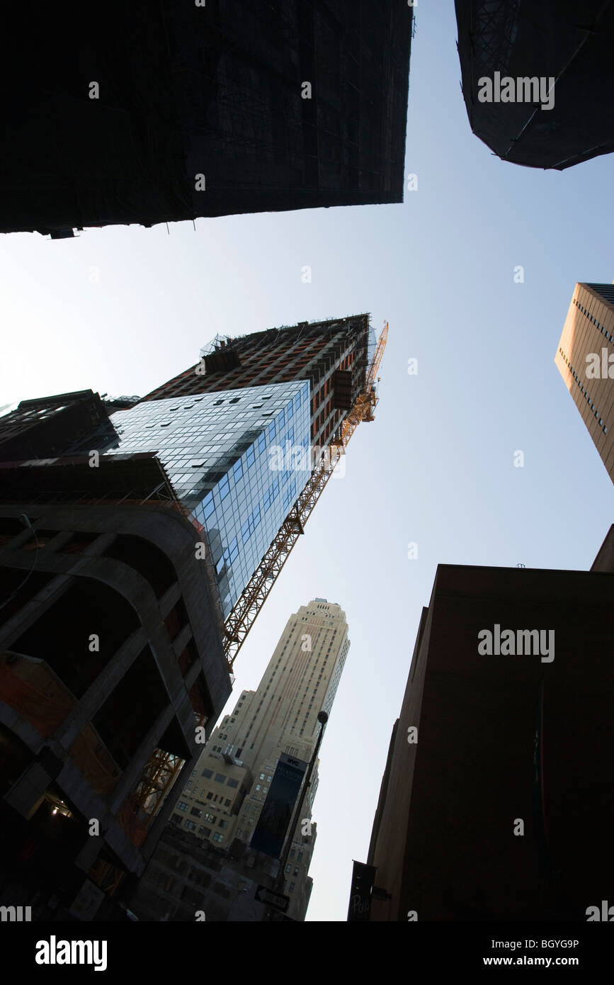 Manhattan skyscraper under construction surrounded by other high rise buildings, low angle view, NYC Stock Photo