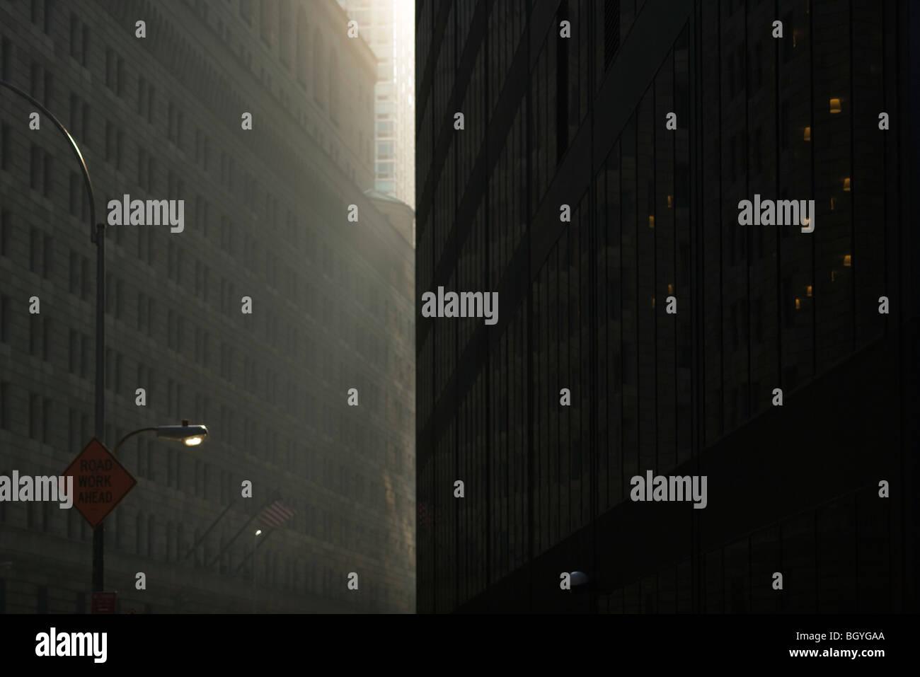 Early morning sunlight illuminating dark city streets hidden between towering high rises, NYC, NY - Stock Image