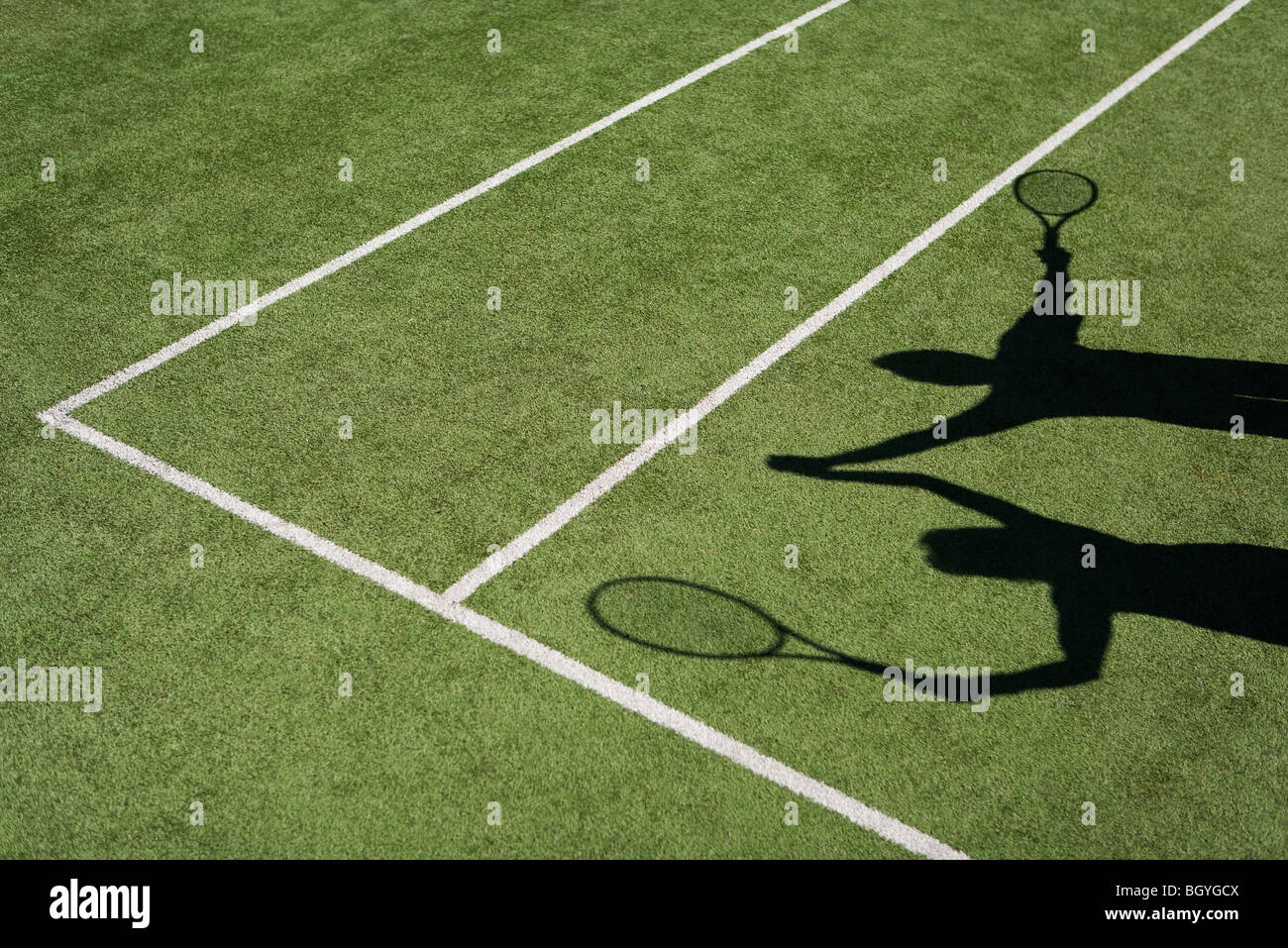 Shadow of tennis players raising clasped hands in celebration - Stock Image