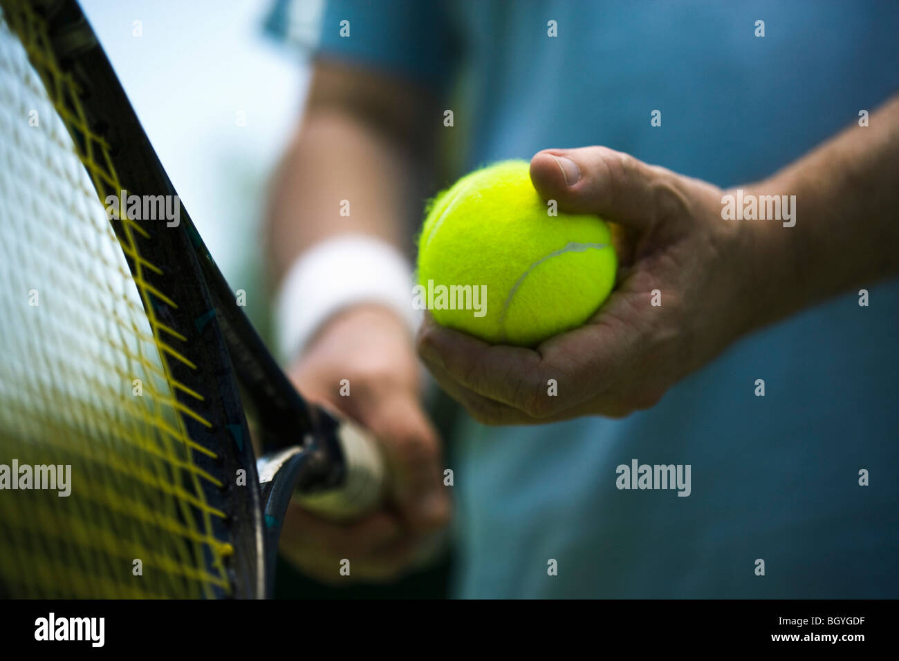 Tennis player preparing to serve, cropped - Stock Image