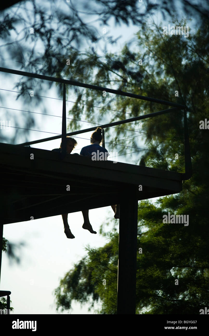 Couple sitting together on deck, legs hanging off edge - Stock Image