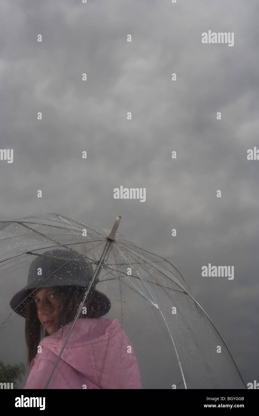 Female with transparent umbrella looking over shoulder at camera - Stock Image