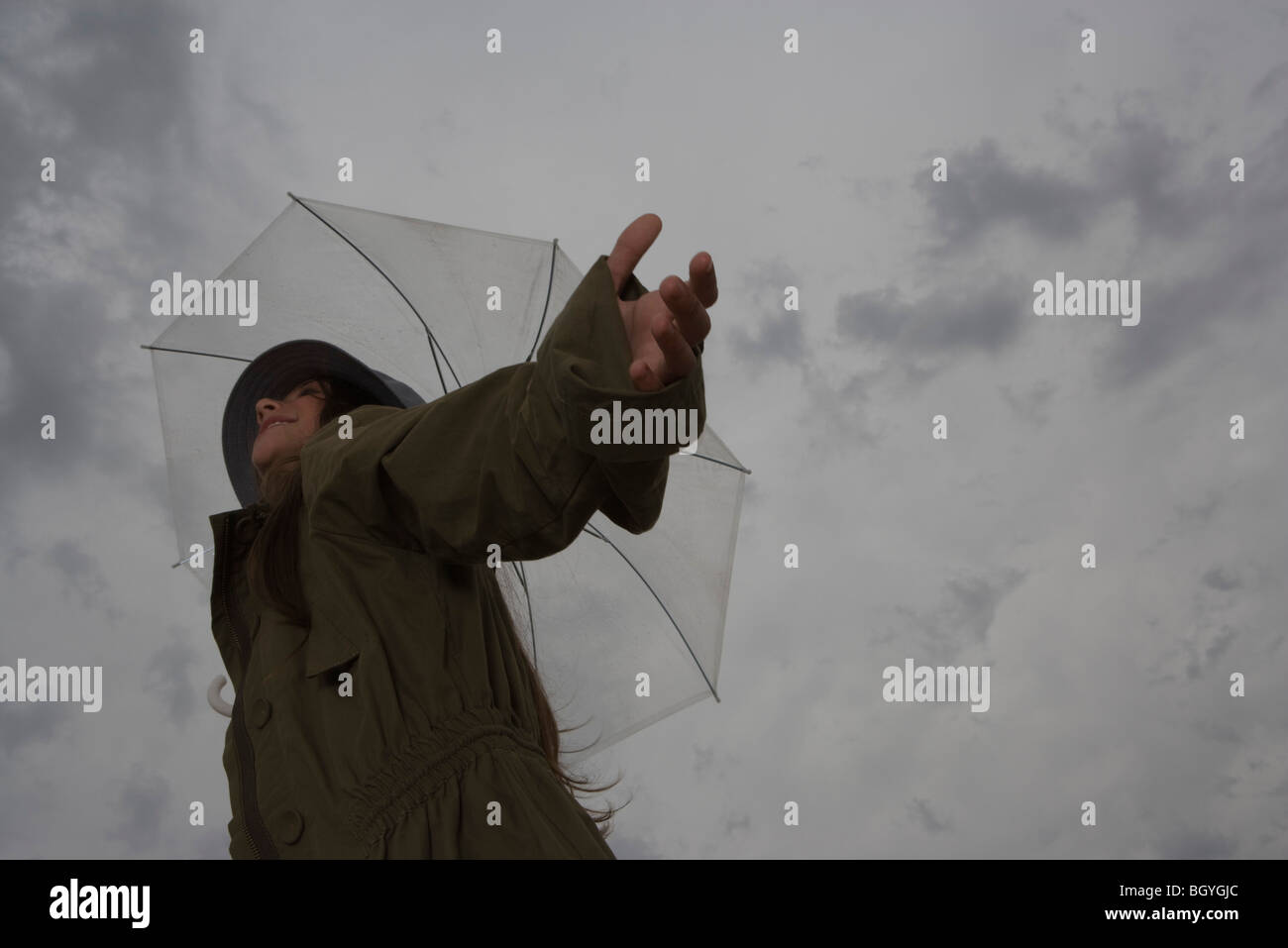 Female with umbrella, arms outstretched and head back, looking away, smiling - Stock Image