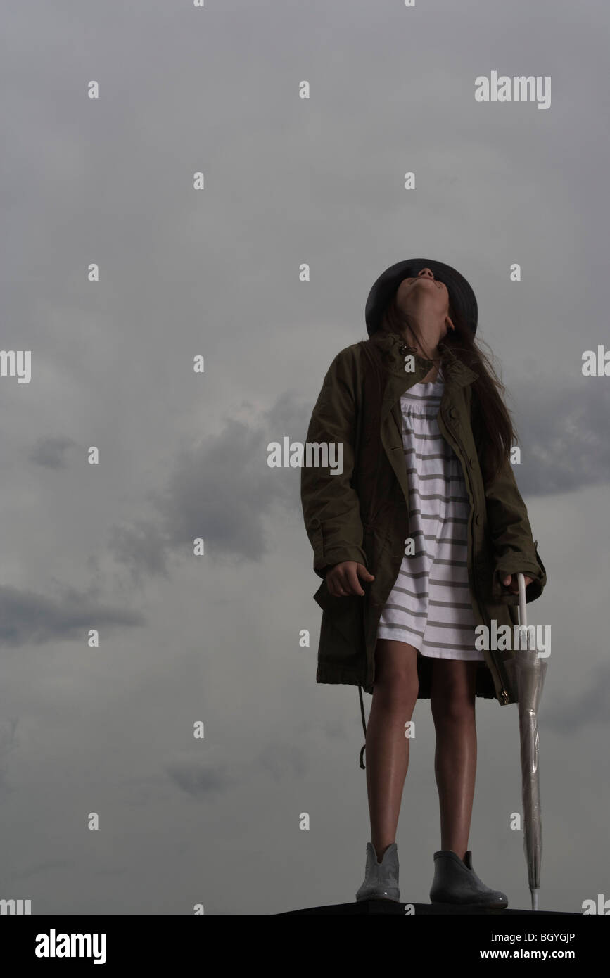 Female with umbrella looking up at cloudy sky - Stock Image