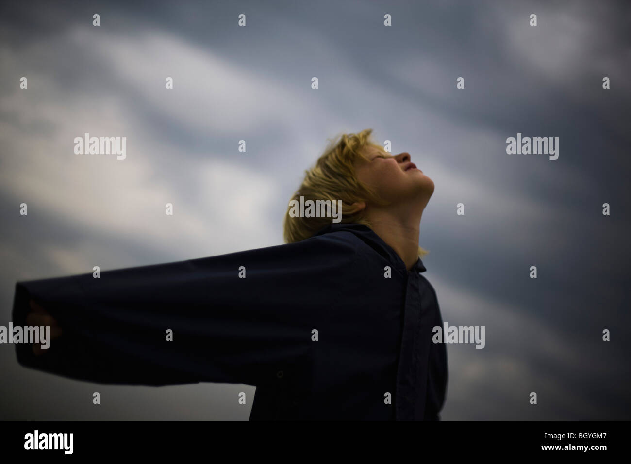 Boy with arms outstretched, head back, looking up at sky - Stock Image