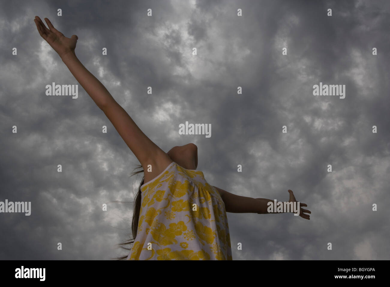 Girl with arms outstretched, head back, looking up at gray sky - Stock Image