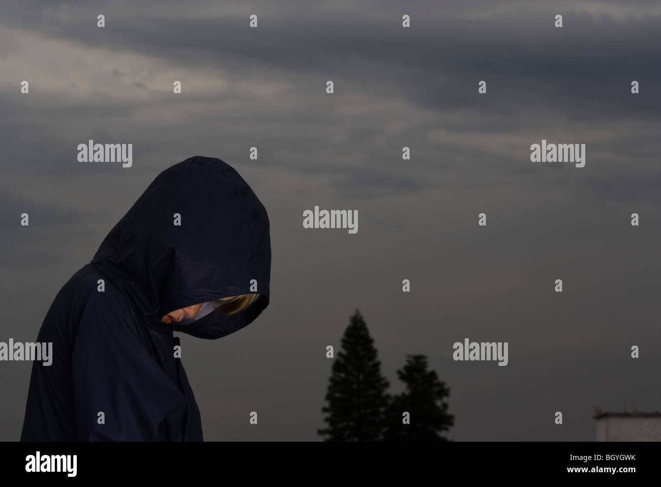 Boy with head down, face obscured by jacket hood - Stock Image