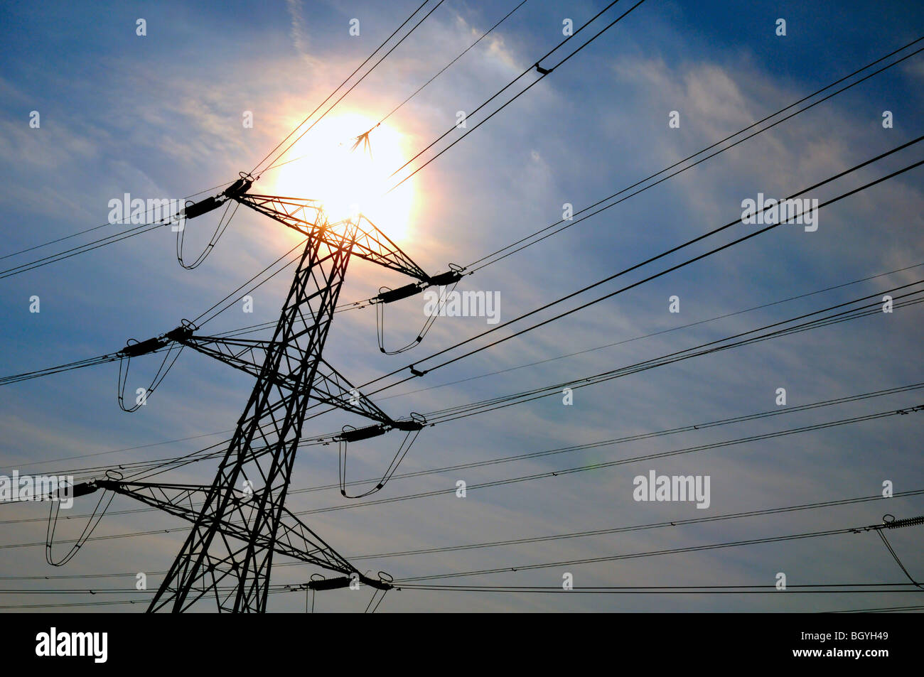 Electricity pylons with sun - Stock Image