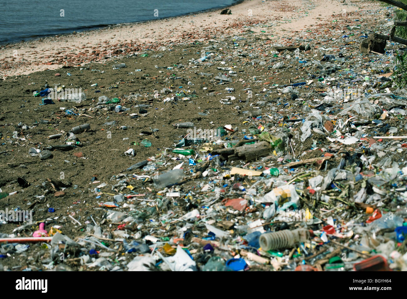 Beach strewn with washed up garbage - Stock Image