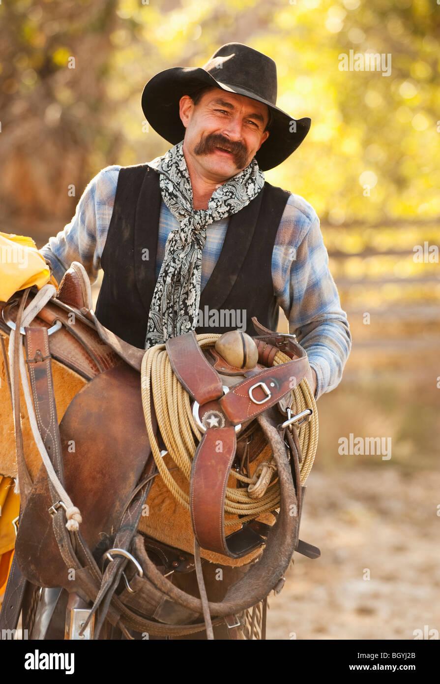 Cowboy holding saddle - Stock Image