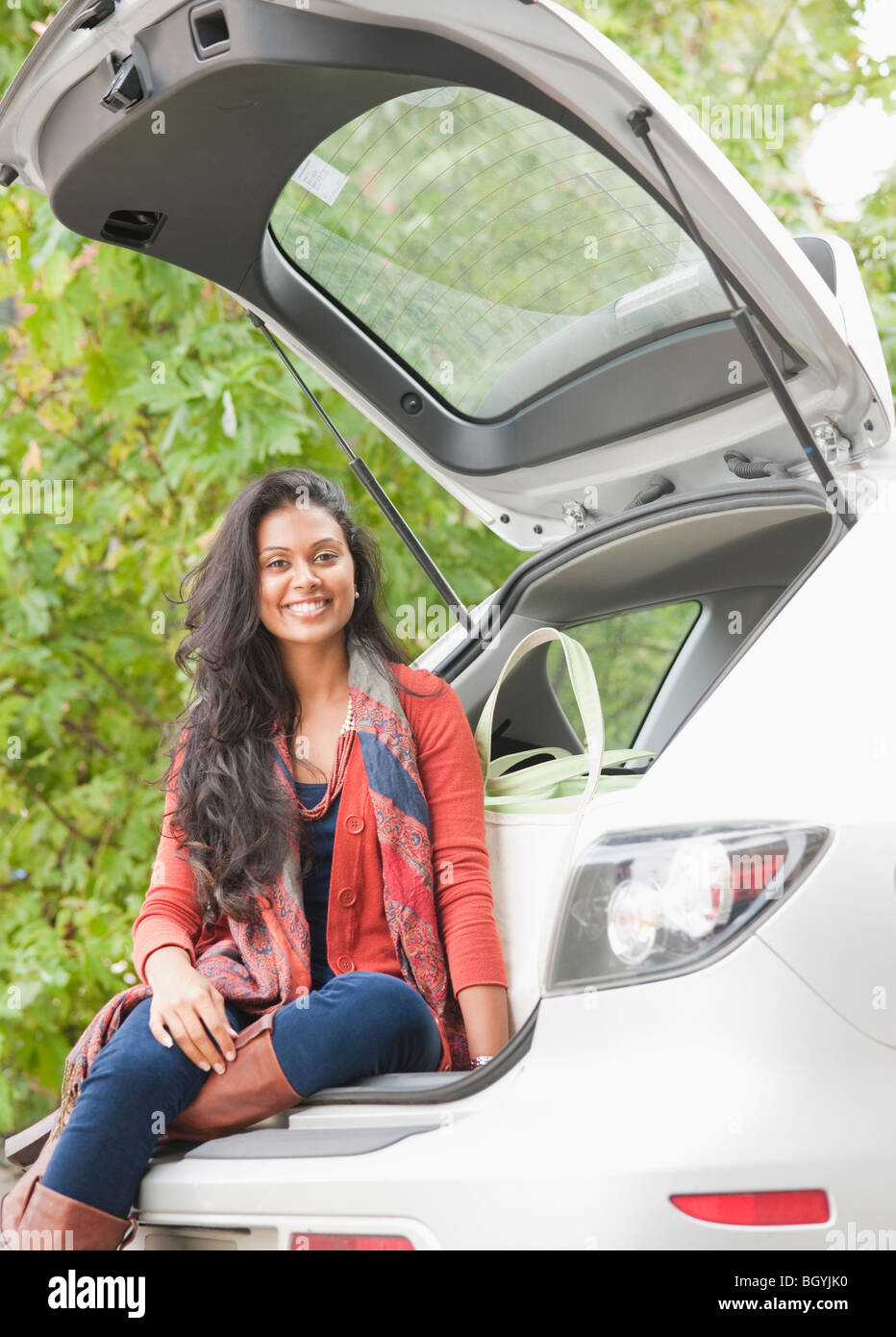 Woman sitting in trunk of car - Stock Image