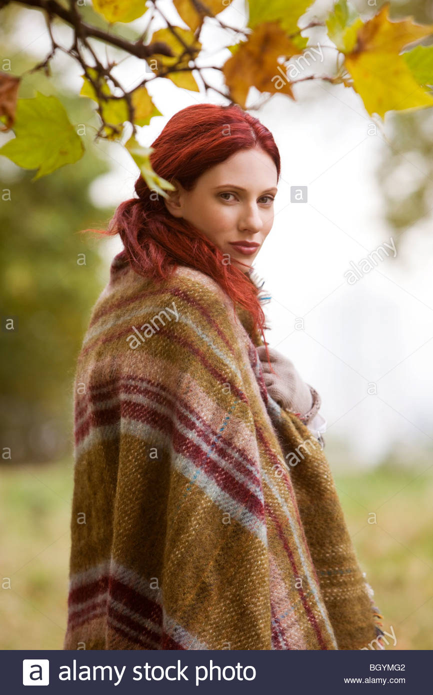 A young woman standing outdoors, wrapped in a blanket - Stock Image