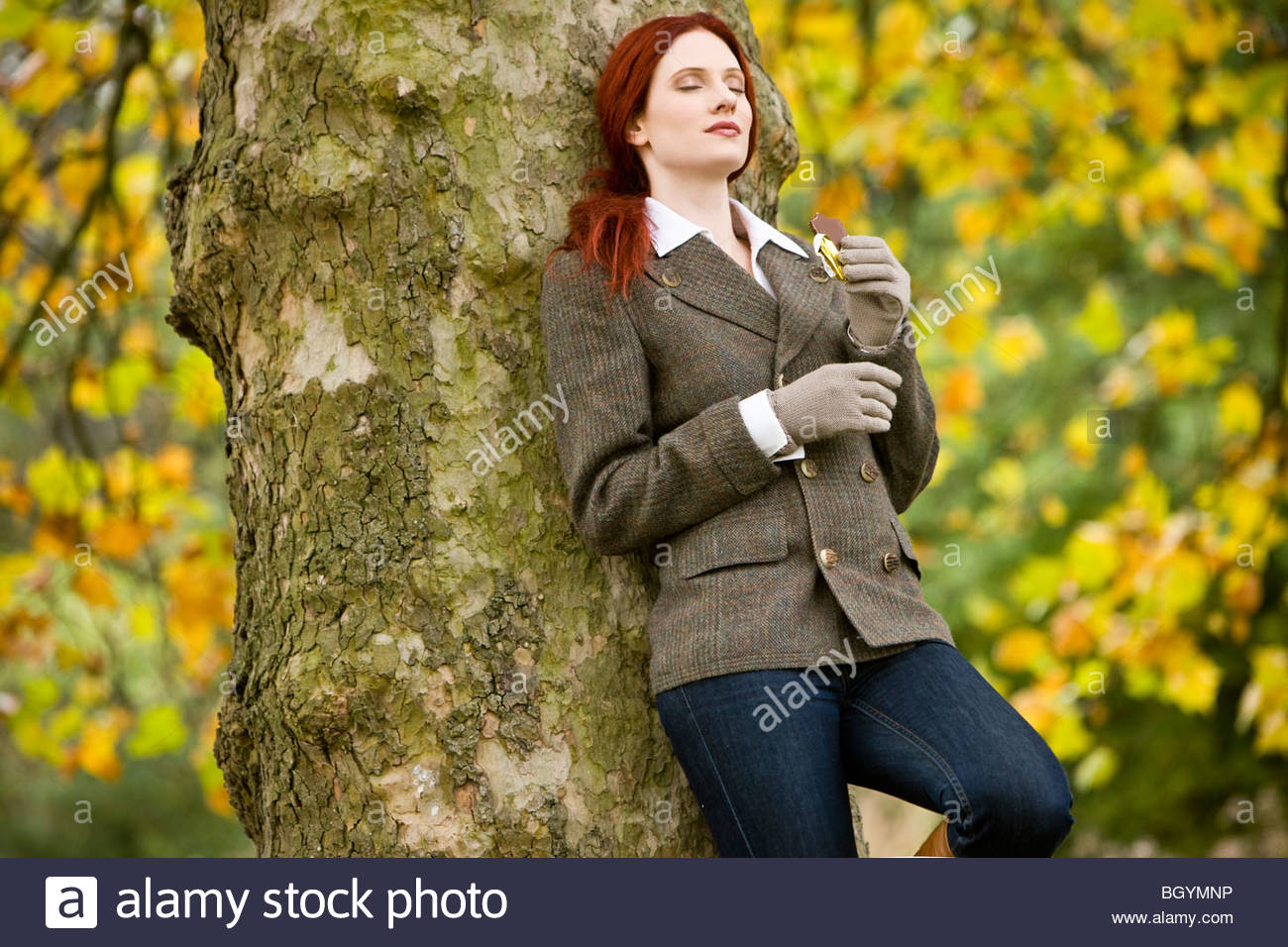 A young woman leaning against a tree, eating chocolate - Stock Image