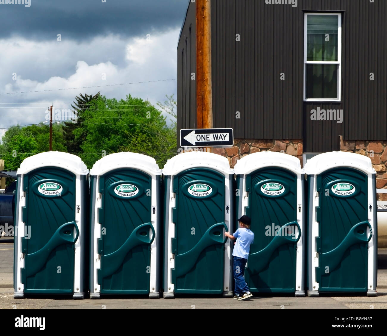 Young boy trying to open the door of a portaloo. Row of 5 mobile toilets Stock Photo