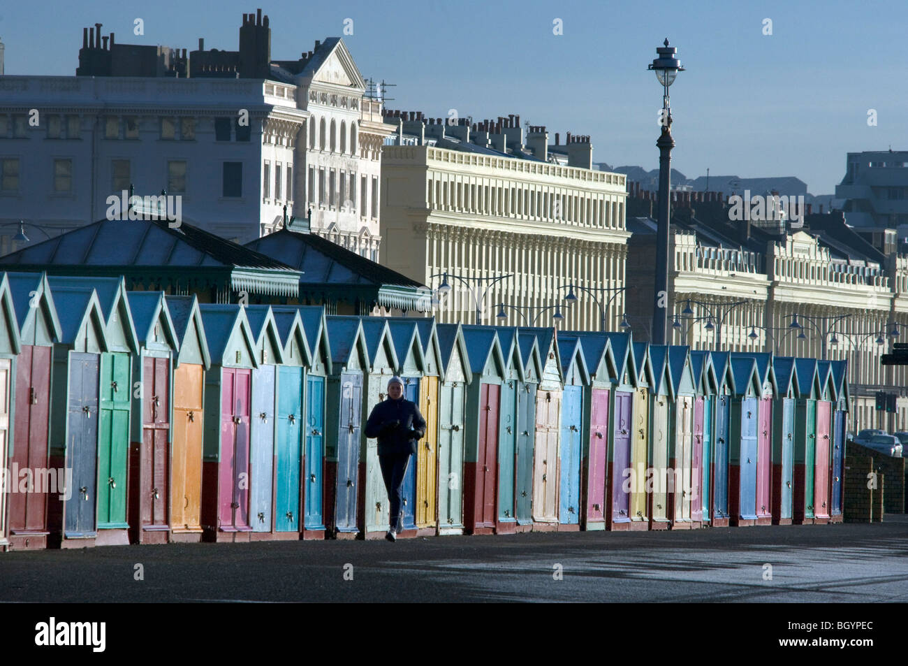 A jogger runs past a row of Beach Huts on Hove seafront promenade - Stock Image