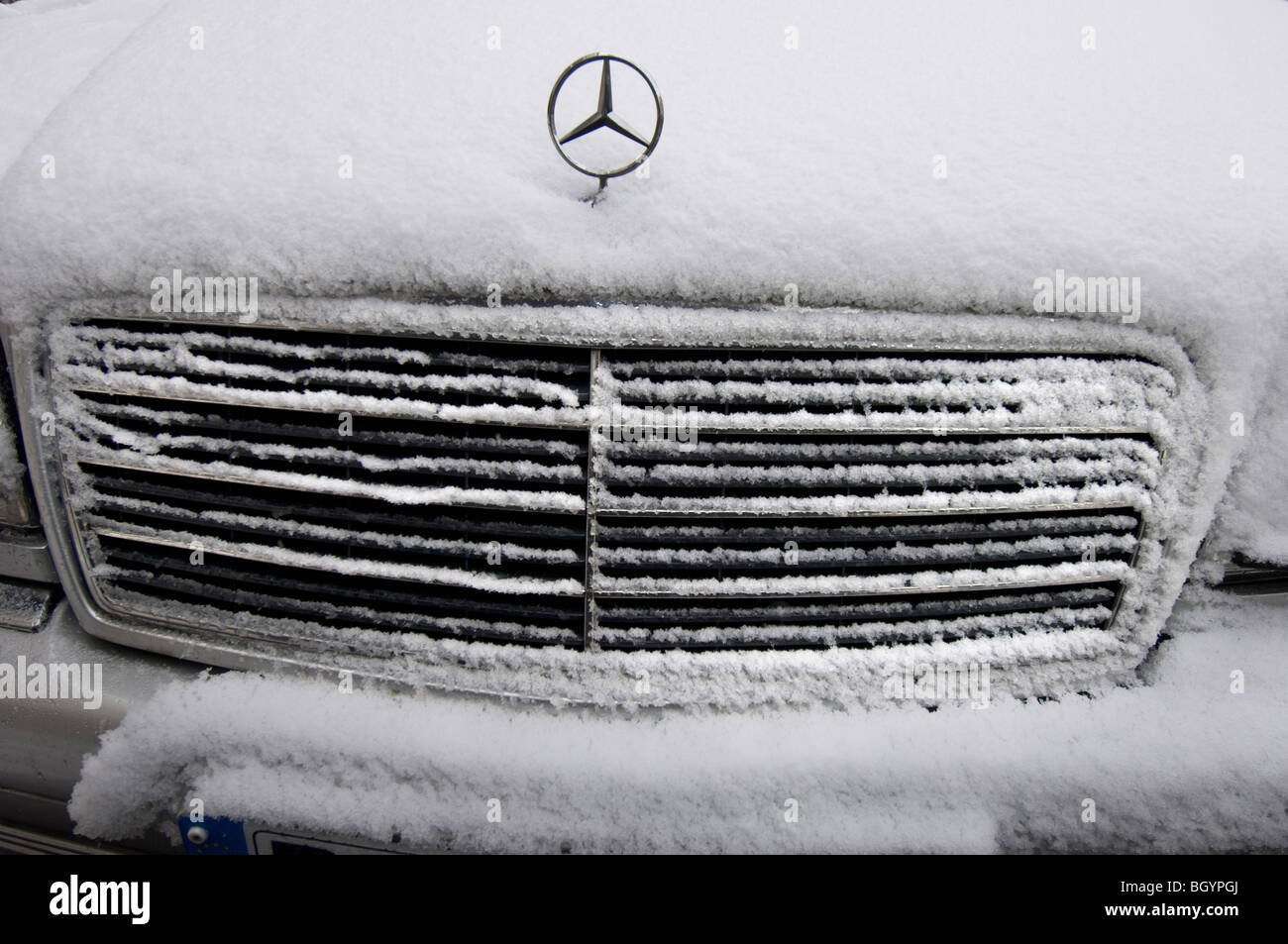 A snow covered MERCEDES car showing the radiator grille and badge Stock Photo