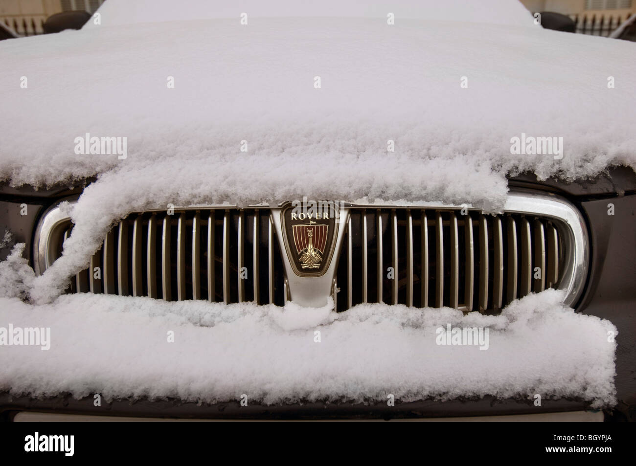 A snow covered Rover car showing the grille and badge - Stock Image