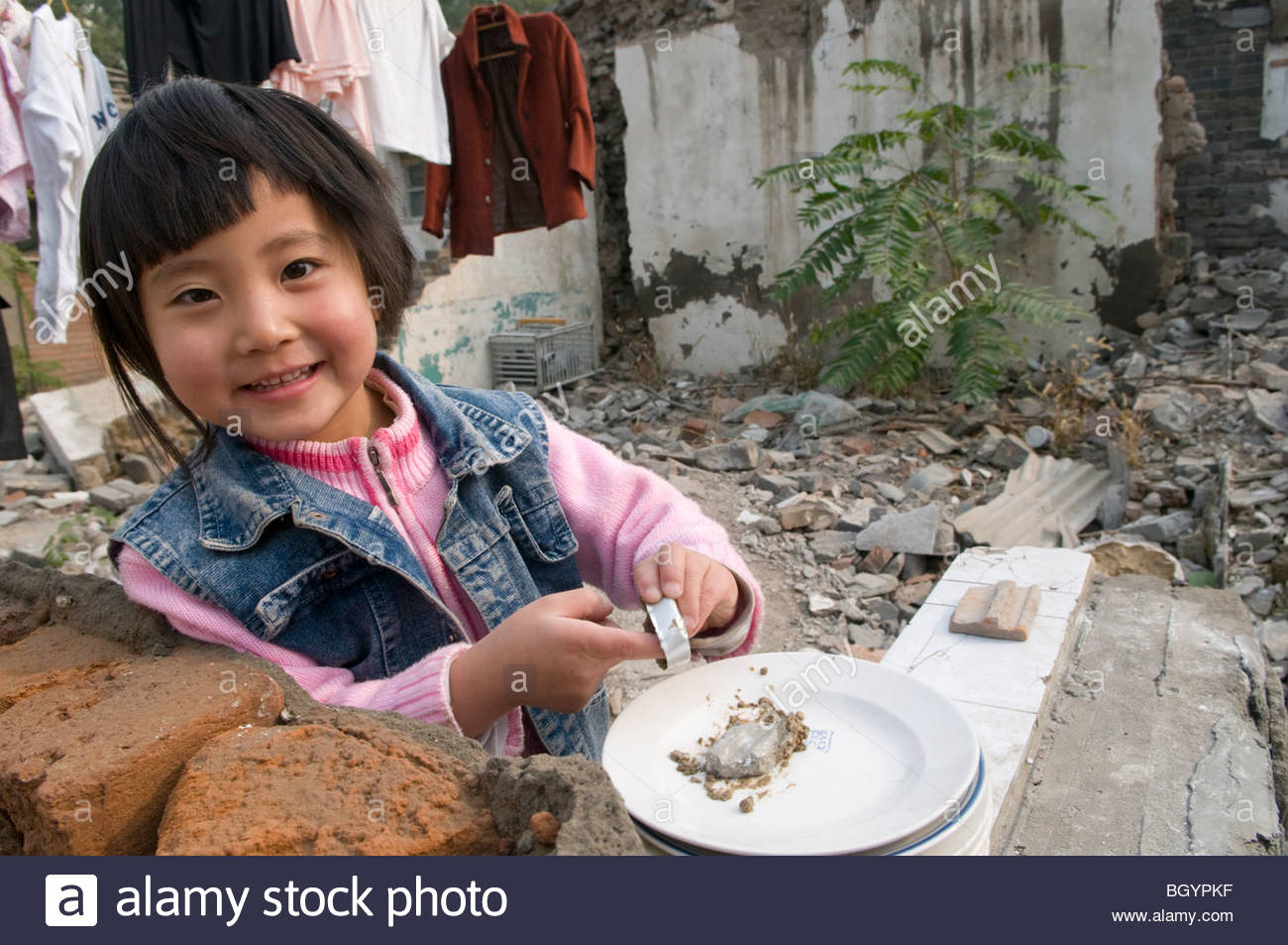 A young girl plays in the courtyard of a demolished hutong in Beijing China - Stock Image