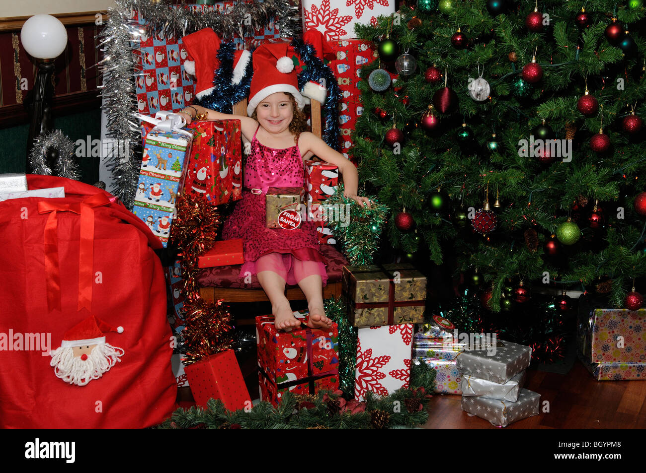 Little girl sitting in Santa\'s chair surrounded by Christmas gifts ...