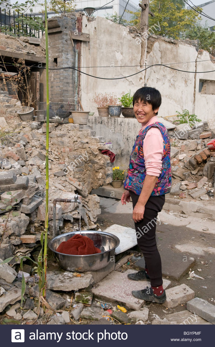 A woman washes laundry in the courtyard of a demolished hutong in Beijing China - Stock Image