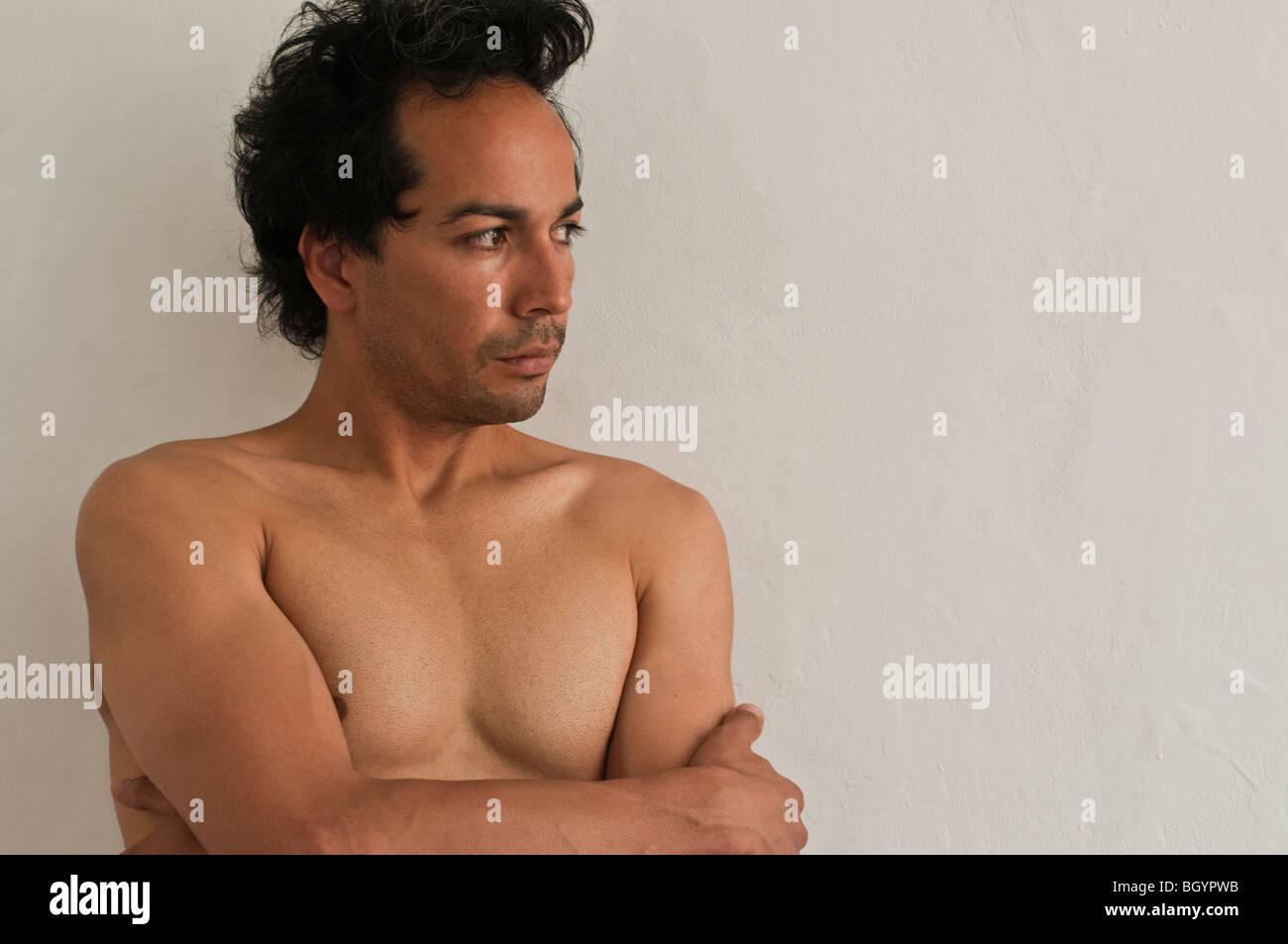 Hunky nude Latino male with arms crossed