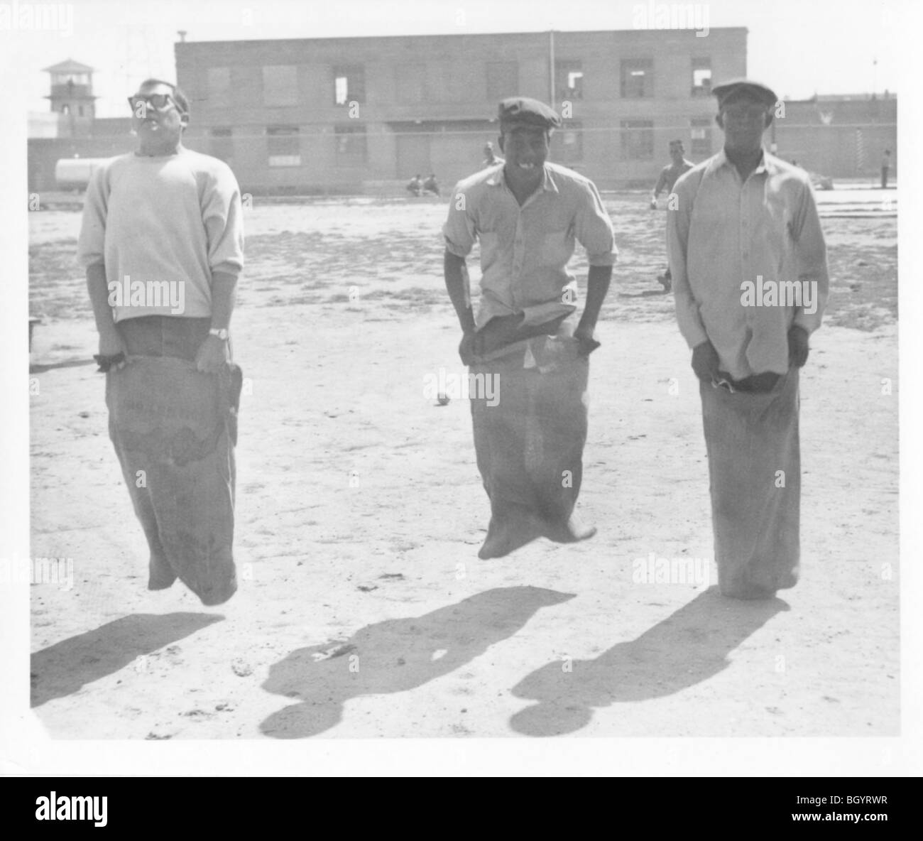 Inmates compete in sack jumping in the prison yard. It was a different atmosphere back then. 1940s to 1960s. Lincoln, - Stock Image