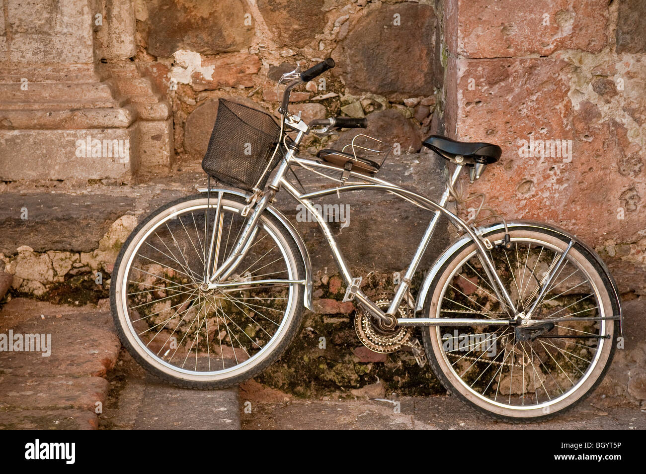 Chrome bicycle against rock wall of church in the town of Tequila, Jalisco, Mexico. - Stock Image