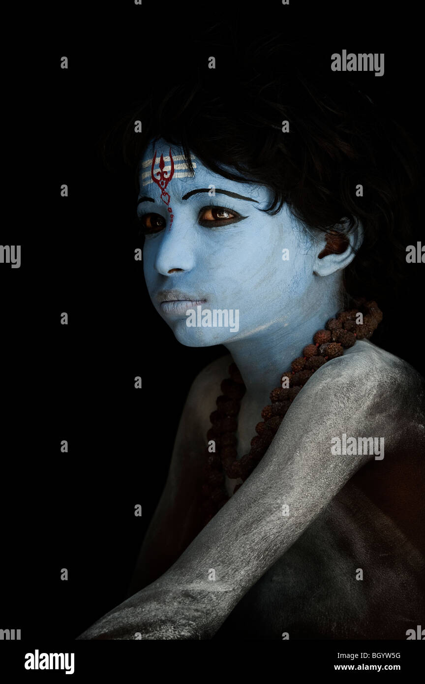 Indian boy, face painted as the Hindu god Shiva against a black background. India - Stock Image