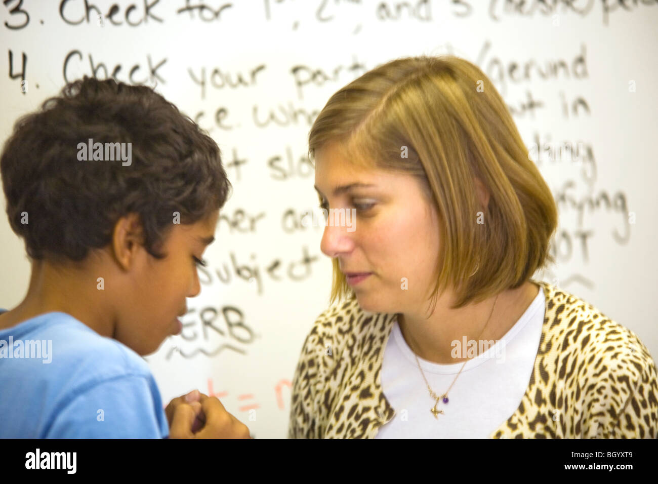 California middle school teacher counsels one of her students. Note white board in background. - Stock Image