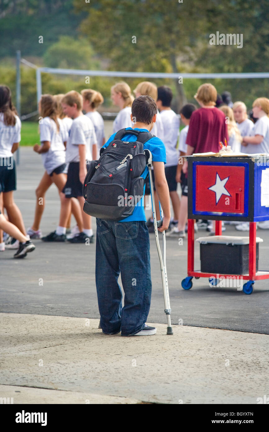 On crutches and unable to participate, a handicapped California middle school student watches a campus physical - Stock Image