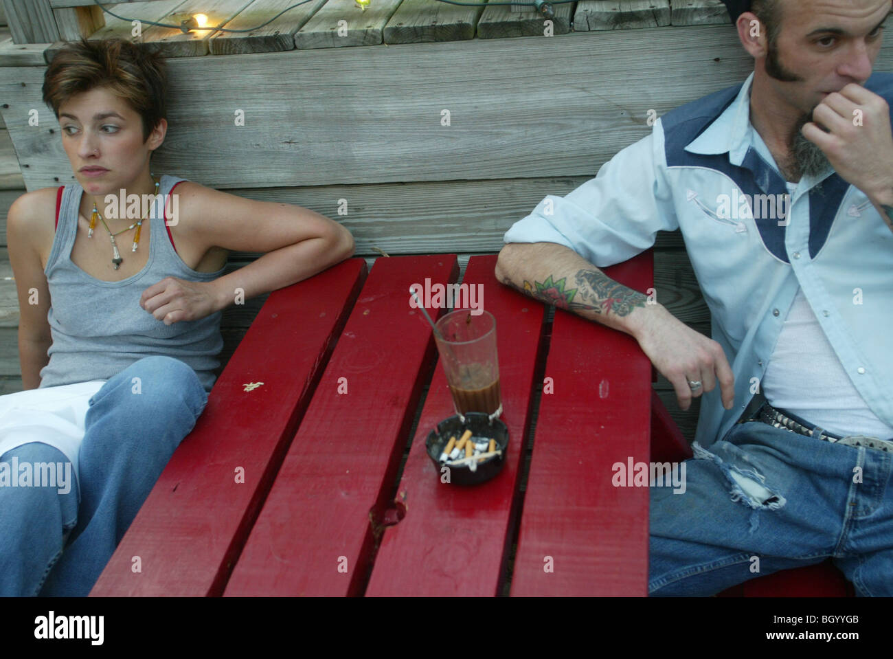 Mia Rae, 24, and Dylan Long, 33, relax on at a table outside SOMA coffee shop in downtown Bloomington. - Stock Image