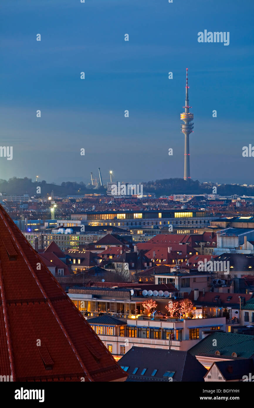 View towards the Olympiaturm (Olympic Tower) over the rooftops of buildings at sunset in the City of München - Stock Image