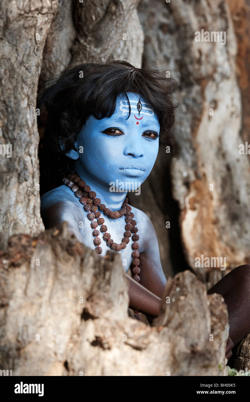 Indian boy, face painted as the Hindu god Shiva sitting in an old tree stump. Andhra Pradesh, India Stock Photo