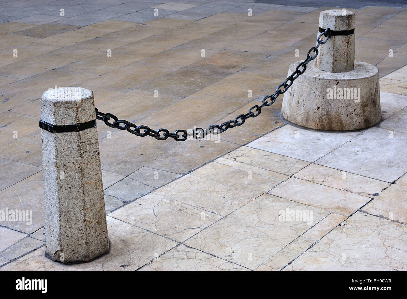 chain and stone bollards to prevent vehicle passage Stock Photo