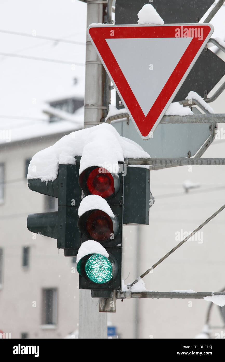 snow-covered traffic lights and yield sign - Stock Image