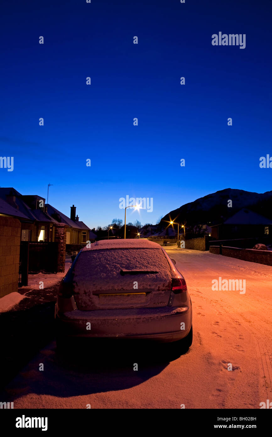 Parked car covered in winter snow under sodium street lighting at dusk - Stock Image