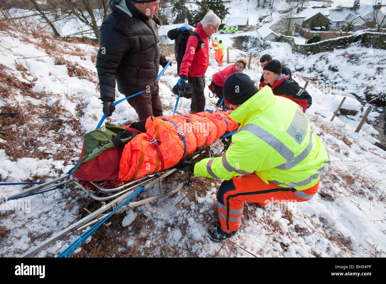 Paramedics and Mountain Rescue team members evacuate an injured walker in the Lake District, UK. - Stock Image
